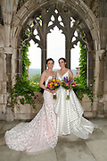 Two beautiful brides posing in front of the ivy decorated, stone arch War Memorial at Cornell University in Ithaca, NY