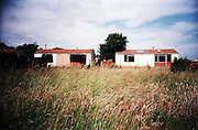 """Abandonned prefabs in Newport, 2003. Thousands of post-war prefabs are still being lived in and cherished by their tenants or owners all over the UK. I  love prefabs. Some people will think living in a prefab is like living in a box. Yes, it might sound or even look a bit like that but what a lovely, sophisticated box! I am talking about post-war prefabs, erected in a hurry just after the war when Britain was suffering an unprecedented housing shortage. More than 150 000 of these prefabricated houses were erected all over the UK mainly ins small estates. They were luxury to most of the residents who mainly were service men coming back from the war and reuniting with their family. Their prefab became their little castle with all mod cons and even more than any working class could hope for at the time: hot water, toilets inside, a fitted kitchen with a gas fridge and a garden all around the house. Part of the temporary housing programme, they were not supposed to last over a decade. Yet, over 70 years later, a few Thousands are still standing and very much loved.<br /> <br /> Why do people love their prefab so much, why are they so attached to their """"cardboard or tin boxes""""? Is it the layout of the prefab, the design of the interior, the garden around? Is the sense of community they created? Or a combination of everything?That's what I have been trying to find out for the last 11 years, since I started taking pictures of prefabs in South London. I have travelled all over the UK, from Redditch to Newport, Chesterfield, Catford and even on the Isle of Lewis to try to draw some answers. I have met wonderful people and come back with their portraits and their moving stories. Here they are for you to discover through this project."""