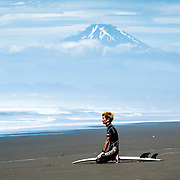 A surfer watches the waves with Mt. Fuji in the background at Shonan Beach in Fujisawa, Kanagawa Prefecture, 50 kilometers south of Tokyo.