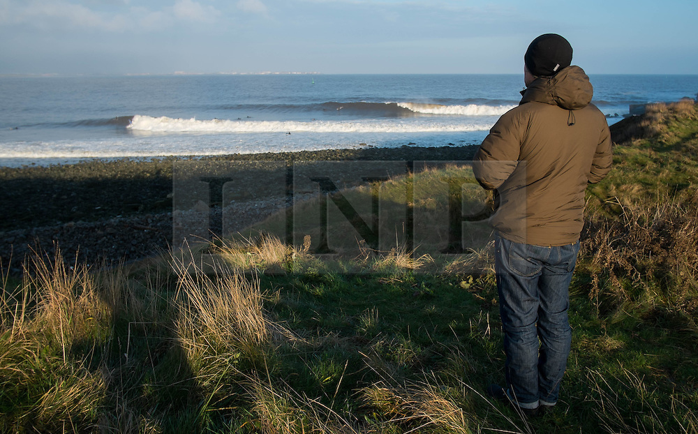 © Licensed to London News Pictures. <br /> 18/11/2014. <br /> <br /> Redcar, United Kingdom<br /> <br /> Surfer Steve Bulmer stands and watches out over the surf near Redcar in Cleveland.<br /> <br /> Photo credit : Ian Forsyth/LNP