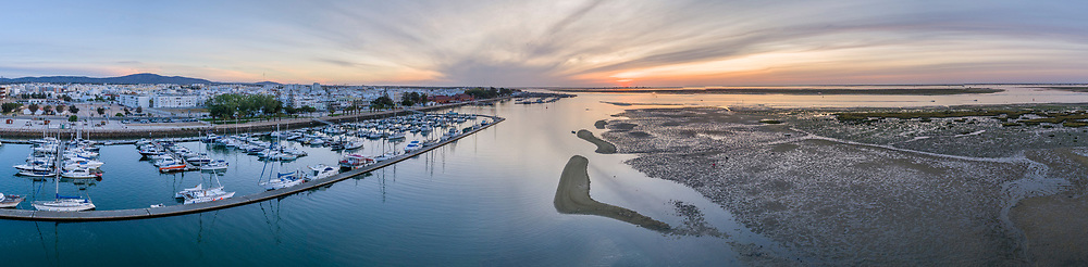 Sunrise aerial seascape view of Olhao Marina, waterfront to Ria Formosa natural park. Algarve. Portugal.