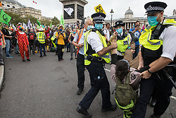Metropolitan Police officers arrest a climate activist from Extinction Rebellion in Trafalgar Square during a 'Carnival of Corruption' protest against the government's facilitation and funding of the fossil fuel industry on 3 September 2020 in London, United Kingdom. Extinction Rebellion activists are attending a series of September Rebellion protests around the UK to call on politicians to back the Climate and Ecological Emergency Bill (CEE Bill) which requires, among other measures, a serious plan to deal with the UK's share of emissions and to halt critical rises in global temperatures and for ordinary people to be involved in future environmental planning by means of a Citizens' Assembly.