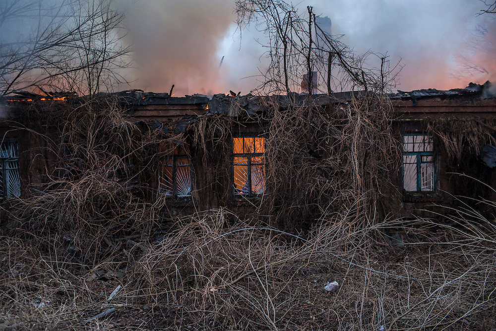 ARTEMIVSK, UKRAINE - FEBRUARY 14: A medical clinic burns after being hit by artillery on February 14, 2015 in Artemivsk, Ukraine. The clinic was closed and there were no reported casualties. A ceasefire between Ukrainian forces and pro-Russian rebels is scheduled to go into effect at midnight. (Photo by Brendan Hoffman/Getty Images) *** Local Caption ***