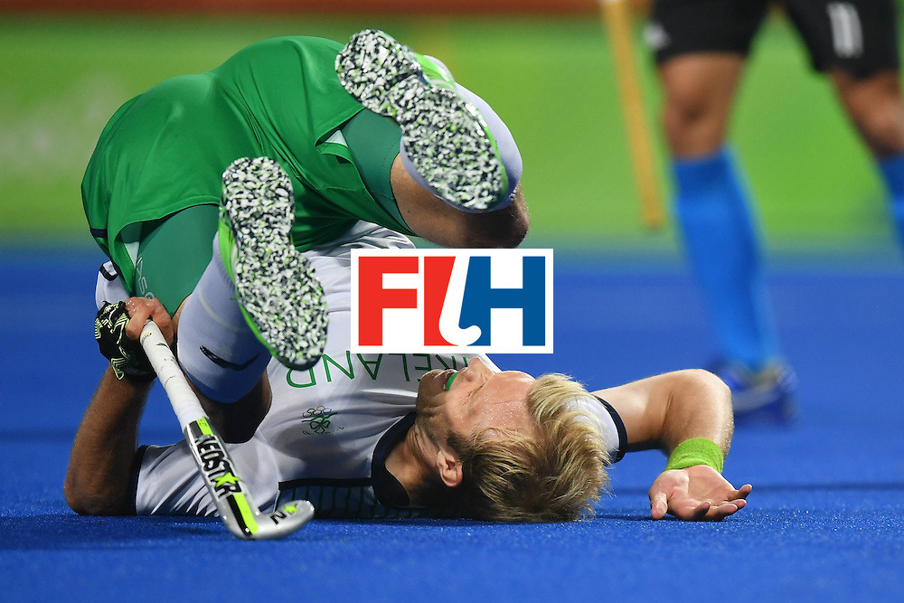 Ireland's Conor Harte falls during the mens's field hockey Ireland vs Argentina match of the Rio 2016 Olympics Games at the Olympic Hockey Centre in Rio de Janeiro on August, 12 2016. / AFP / MANAN VATSYAYANA        (Photo credit should read MANAN VATSYAYANA/AFP/Getty Images)