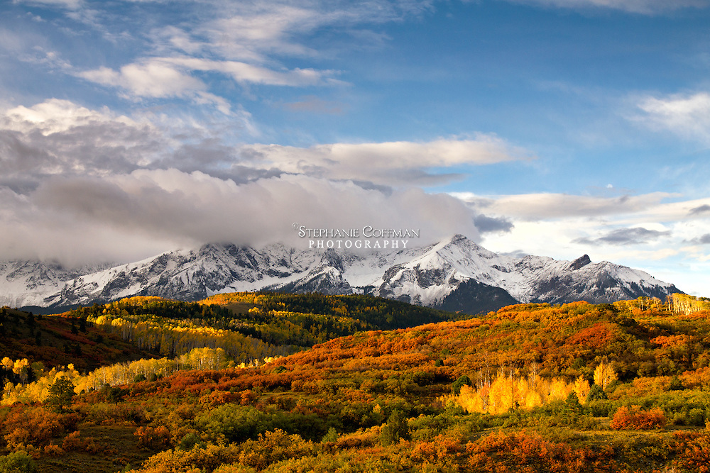 The rising sun lights up the changing leaves of aspen and scrub brush below the Mt. Sneffels range in Colorado
