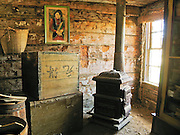 "A Chinese portrait hangs by an old wood stove and boxes in a frontier cabin built in 1890 in Butte and moved to the outdoor history museum of Nevada City, Montana, USA. In 1870, Chinese people (nearly all male) made up 10% of the territorial population of Montana. Territorial laws prohibited ""China Men"" from owning placer claims, so they mined the leavings of others or performed laundry or domestic service, which was always in great demand. Today Nevada City contains several fascinating Chinese buildings built about 1890, mostly moved here from Butte, Montana. Nevada City was a booming placer gold mining camp from 1863-1876, but quickly declined into a virtual ghost town. This fascinating town inspires you to imagination what life must have been like in early Montana when gold was discovered at nearby Alder Gulch. More than 90 buildings from across Montana have been gathered for preservation at Nevada City, mostly owned by the people of the State of Montana, and managed by the Montana Heritage Commission. In 2001, the excellent PBS television series ""Frontier House"" used one of the buildings and its furnishings to train families in re-creating pioneer life. A miner's court trial and hanging of George Ives in the main street of Nevada City was the catalyst for forming the Vigilantes, a group of citizens famous for taking justice into their own hands in 1863-1864. Directions: go 27 miles southeast of Twin Bridges, Montana on Highway 287."