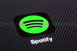 Spotify music cloud based streaming service app close up on iPhone smart phone screen
