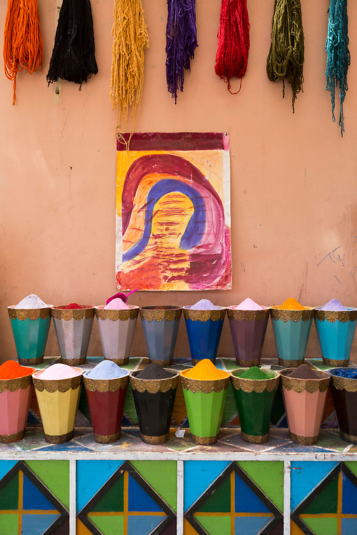 MARRAKESH, MOROCCO - May 30th 2018 - Colourful fabrics and materials hang for sale next to powdered paints and pigments in the Mellah, Marrakech Medina, Morocco