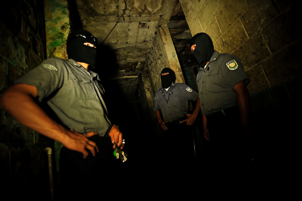Guards control a hallway in Izalco men's prison at night. Guards are required to wear black ski masks in order to remain anonymous for security purposes.