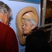 Raadszaal Huizen zintuigtest ouderen en knoppenwinkel gemeentehuis Huizen, vrouw luisterend aan een groot oor, gehoortest