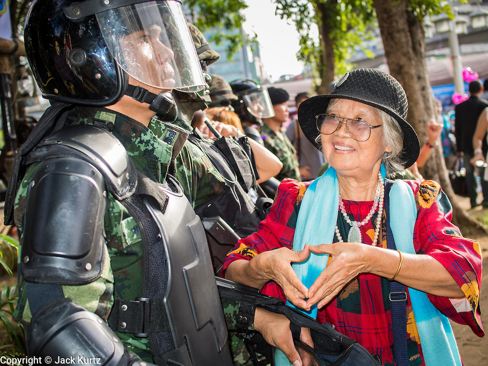 """15 JUNE 2014 - BANGKOK, THAILAND:  A woman makes a heart with her hands after posing for photos with Thai military special operations soldiers during public relations """"Return Happiness to Thais"""" party in Lumpini Park in Bangkok. The Thai military junta, formally called the National Council for Peace and Order (NCPO), is sponsoring a series of events throughout Thailand to restore """"Happiness to Thais."""" The events feature live music, dancing girls, military and police choirs, health screenings and free food.  PHOTO BY JACK KURTZ"""
