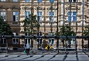 A pedestrian and cyclist for the Slovenian postal service (Posta Slovenije) outside the main post office on Slovenska Cesta (street) in the Slovenian capital, Ljubljana, on 25th June 2018, in Ljubljana, Slovenia.