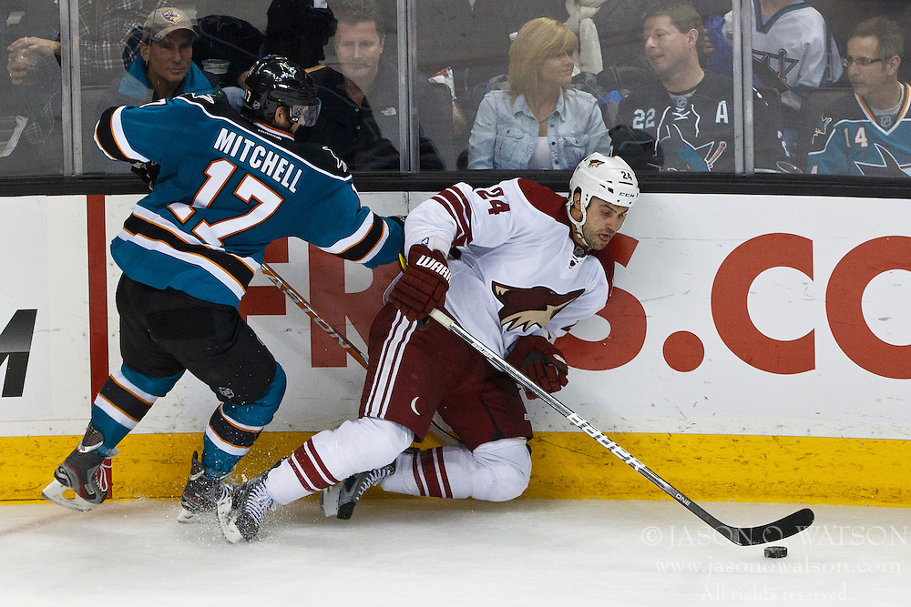 Mar 24, 2012; San Jose, CA, USA; San Jose Sharks left wing Torrey Mitchell (17) checks Phoenix Coyotes center Kyle Chipchura (24) during the third period at HP Pavilion.  San Jose defeated Phoenix 4-3 in shootouts. Mandatory Credit: Jason O. Watson-US PRESSWIRE