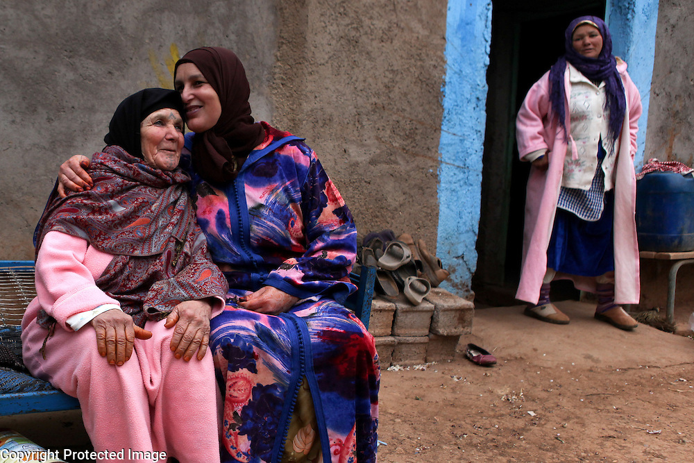 From left, Khina Boujnoui and her daughter, Fatima, share a moment of affection outside the family's home in Tamda, Morocco. The women are part of a traditional Berber family that has been weaving for generations.