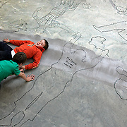 Hidden Valley School student Connor Cottrell-Tribes gets his outline drawn on the concrete floor by classmate Romney Duncan on Thursday. The signed outlines will serve as a time-capsule after the school's carpeting is installed this weekend.