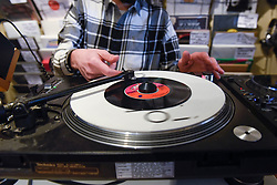 © Licensed to London News Pictures. 13/04/2019. LONDON, UK. A DJ plays a single in Phonica Records. Analogue music fans visit independent record shops in Soho to celebrate vinyl music on the 12th Record Store Day.  Over 200 independent record shops across the UK come together annually to celebrate the unique culture of analogue music with special vinyl releases made exclusively for the day.  In 2018, sales of vinyl rose for the 11th consecutive year to 4.2 million units according to the British Phonographic Industry (BPI).  Photo credit: Stephen Chung/LNP