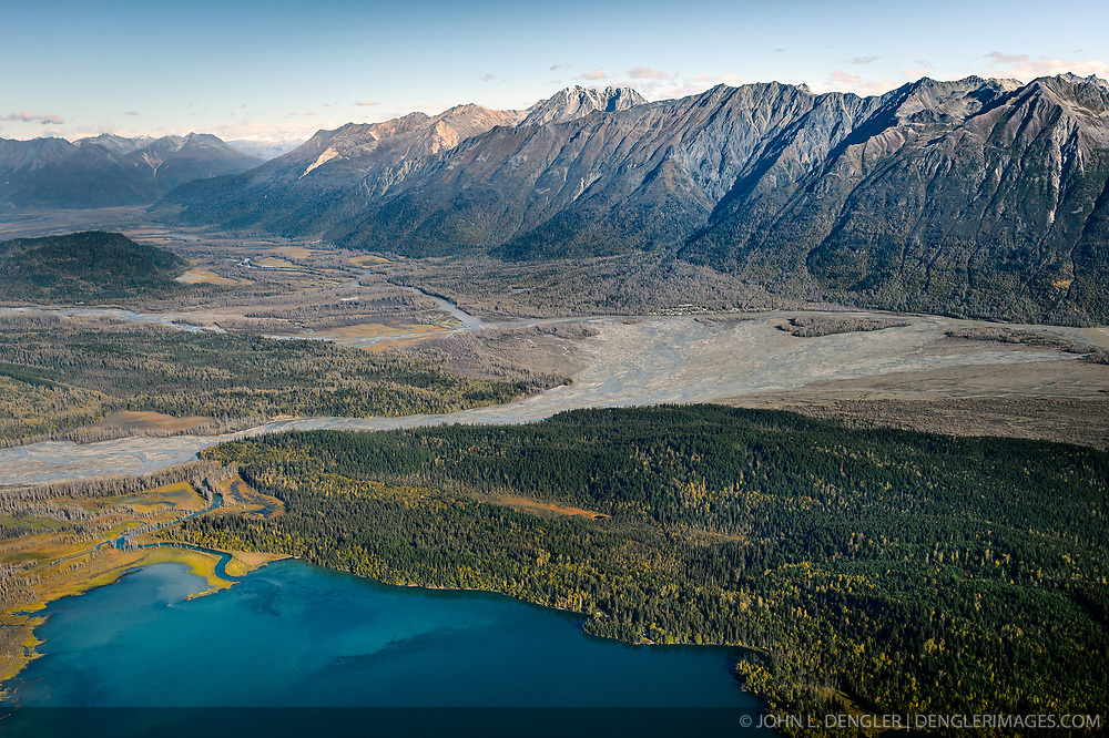 "This aerial photograph of a portion of the ""Council Grounds"" is the primary area where bald eagles gather on the Chilkat River in the Alaska Chilkat Bald Eagle Preserve near Haines, Alaska. Bald eagles come to the alluvial delta area at the confluence of the Tsirku (center) and Chilkat (upper left to right) Rivers because of the availability of spawned-out salmon and open waters in late fall and early winter. The open water is due to a deep accumulation of gravel and sand that acts as a large water reservoir whose water temperature remains 10 to 20 degrees warmer than the surrounding water temperature. This warmer water seeps into the Chilkat River, keeping a five mile stretch of the river from freezing. Photographers come to the Chilkat River in November and December to photograph one of the largest gatherings of bald eagles in the world. In 1982, the 48,000 acre area was designated as the Alaska Chilkat Bald Eagle Preserve. In the background are the mountains that make of the Takshanuk Mountains. Chilkat Lake is pictured in the foreground. River on the left above the Tsirku River is the Klehini River which joins the Chilkat River right before the Tsirku River alluvial fan. Also pictured is Klutshah Mountain (top center), Iron Mountain and the village of Klukwan (in front of the left side of the alluvial fan)."