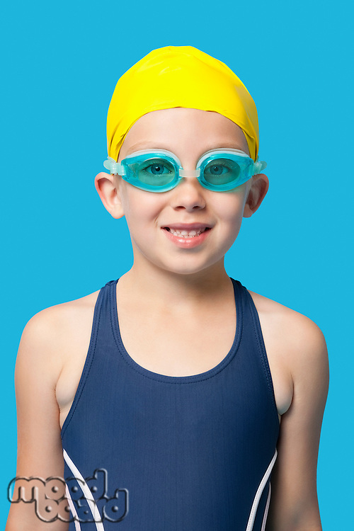 portrait of a happy young girl wearing swim goggles over blue background