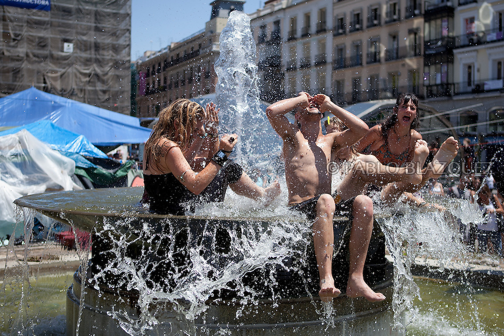People refresh from the heat in a fountain at the Puerta del Sol Square in Madrid on June 12, 2011. Protesters installed in Madrid's Puerta del Sol square for the previous month are scheduled to dismantle today their ramshackle encampment, which has become a symbol of the anti-establishment movement.