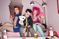 Handsome guy holding playing cards with tattooed women sitting besides