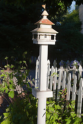 White bird house with metal roof and flag on top near sidewalk next to white picket fence.