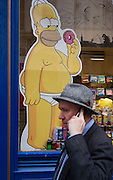 Homer Simpson cartoon character and passer-by holding mobile phone in central London.