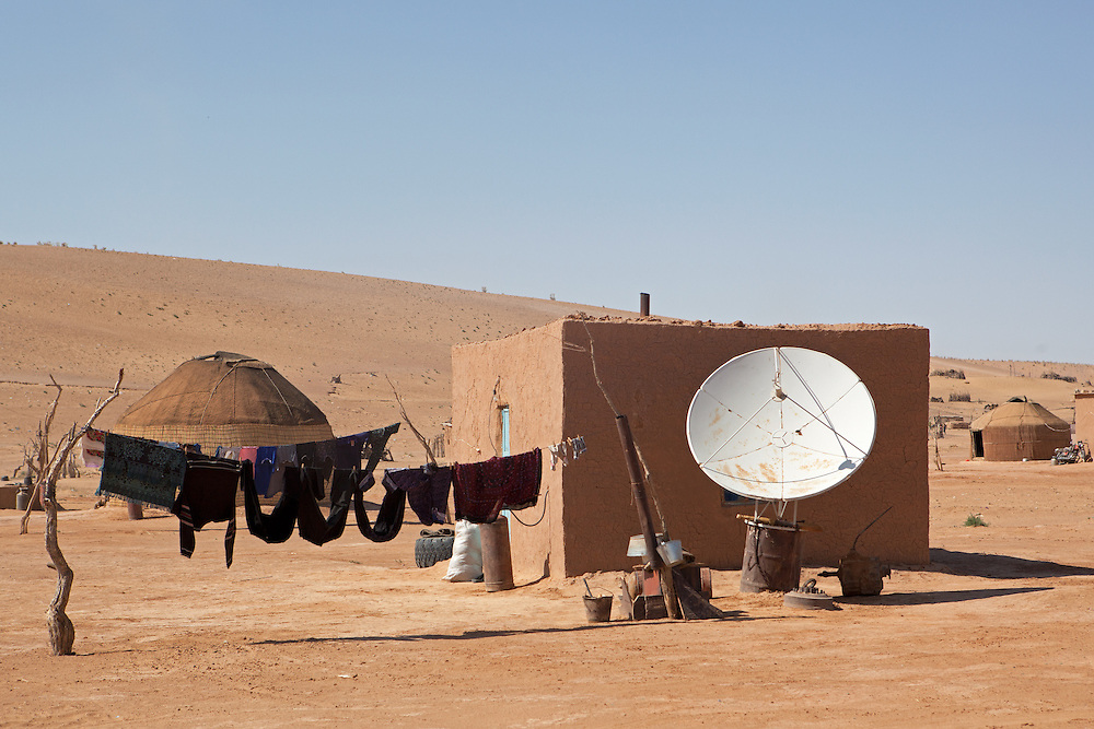 A satellite dish stands outside a desert home in the Karakum Desert, Turkmenistan
