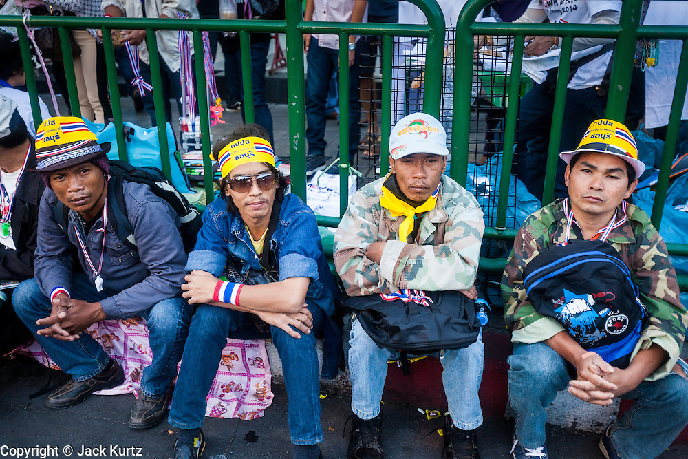 "13 JANUARY 2014 - BANGKOK, THAILAND: Members of the anti-government protest movement sit on the curb in the Asoke intersection in Bangkok. Tens of thousands of Thai anti-government protestors took to the streets of Bangkok Monday to shut down the Thai capitol. The protest was called ""Shutdown Bangkok"" and is expected to last at least a week. The Shutdown Bangkok protest is a continuation of protests that started in early November. There have been shootings almost every night at different protests sites around Bangkok, including two Sunday night, but the protests Monday were peaceful. The malls in Bangkok stayed open Monday but many other businesses closed for the day and mass transit was swamped with both protestors and people who had to use mass transit because the roads were blocked.    PHOTO BY JACK KURTZ"