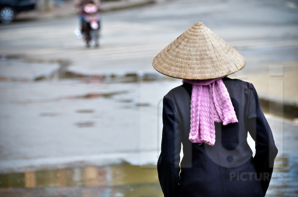 View from behind of a woman wearing a grey suit, a pink scraf and a traditional vietnamese hat. She's walking in a street after the rain, with her hands in her pockets,  in Sapa, Lao Cai province, North Vietnam.