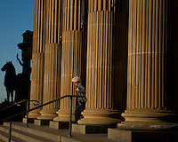 A woman walks down the steps of the NSW Art Gallery in the late afternoon light in Sydney's inner city area called The Domain.
