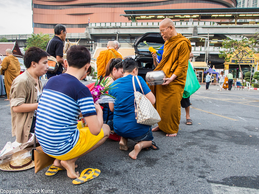 "14 FEBRUARY 2014 - BANGKOK, THAILAND:  Thai Buddhists make merit on Makha Bucha Day at Wat That Thong (also called Wat Tad Tong) in Bangkok. The aims of Makha Bucha Day are: not to commit any kind of sins, do only good and purify one's mind. It is a public holiday in Cambodia, Laos, Myanmar and Thailand. Many people go to the temple to perform merit-making activities on Makha Bucha Day. The day marks four important events in Buddhism, which happened nine months after the Enlightenment of the Buddha in northern India; 1,250 disciples came to see the Buddha that evening without being summoned, all of them were Arhantas, Enlightened Ones, and all were ordained by the Buddha himself. The Buddha gave those Arhantas the principles of Buddhism, called ""The ovadhapatimokha"". Those principles are:  1) To cease from all evil, 2) To do what is good, 3) To cleanse one's mind. The Buddha delivered an important sermon on that day which laid down the principles of the Buddhist teachings. In Thailand, this teaching has been dubbed the ""Heart of Buddhism.""   PHOTO BY JACK KURTZ"