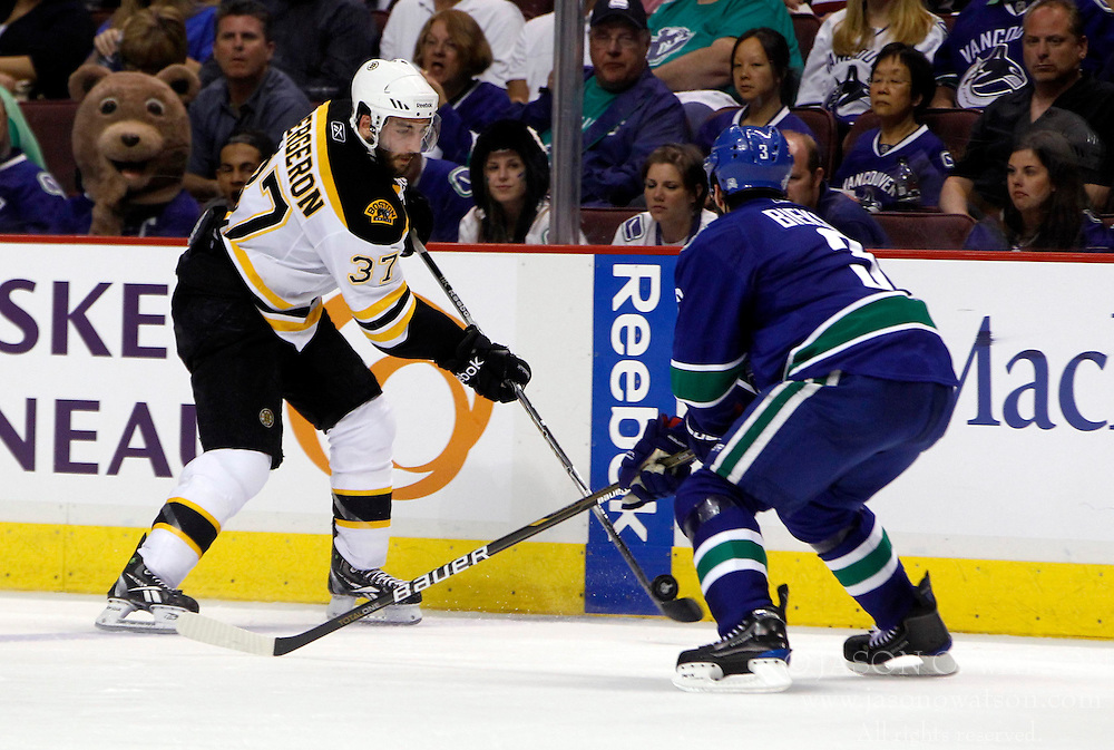 June 4, 2011; Vancouver, BC, CANADA; Boston Bruins center Patrice Bergeron (37) shoots the puck past Vancouver Canucks defenseman Kevin Bieksa (3) during the second period in game two of the 2011 Stanley Cup Finals at Rogers Arena. Mandatory Credit: Jason O. Watson / US PRESSWIRE
