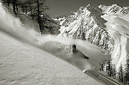 Sport.Male skier turning in fresh powder snow, Serre Chevalier ski resort, France.