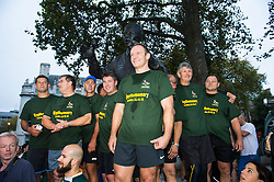 © London News Pictures. 24/10/2015. London, UK. Captain of the 1995 South African Rugby World Cup winning team, FRANCOIS PIENAAR (centre) and other members of the winning team sing the national anthem stood around a statue of Nelson Mandela, mid-way through taking part in an early morning, 2 mile run around westminster to mark the anniversary of in the 1995 winning team going for a morning jog. The event takes place on the morning of the Rugby World Cup semi-final between South Africa and New Zealand. Photo credit: Ben Cawthra /LNP
