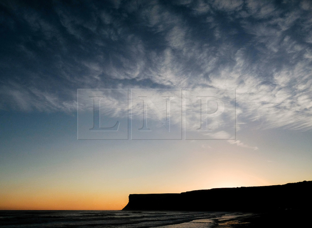 © Licensed to London News Pictures. <br /> 03/10/2016. <br /> Saltburn-by-the-Sea, UK.  <br /> <br /> The sun begins to rise behind Huntcliff on a cold October morning at Saltburn-by-the-Sea.<br /> <br /> Photo credit: Ian Forsyth/LNP