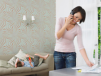 Woman using cell phone boy playing with toy