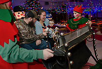 Paul, Eliza and Ella ring the bells as they take off for the North Pole in Santa's sleigh with the help of Hot Cocoa and Egg Nog during opening night of the annual Christmas Village.  (Karen Bobotas/for the Laconia Daily Sun)