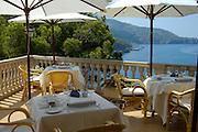 Spanien Spain,Mallorca Balearen..Deia..Restaurant Bens d'Avall, Terrasse mit gedecktem Tisch ueber blauem Meer..restaurant terrace over blue sea....