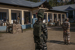 October 8, 2018 - Srinagar, Indian Administered Kashmir, India - Indian government forces stand guard as Kashmiris enter a polling station to cast their votes during the first phase of municipal polls, in Budgam west of Srinagar, the summer capital of Indian administered Kashmir, India.   Indian-administered Kashmir shut on the call of pro-independence groups to mark the first phase of municipal polls being held by India in the disputed Himalayan region on Monday. The restive Kashmir valley witnessed just 17.5 polling percentage till 3 pm, officials said.  Pro-independence groups had called for a shutdown to mark the polls while pro-India parties like the National Conference and People's Democratic Party decided to stay away from the process, citing New Delhi's attempts to alter the special status accorded to the region in the Indian constitution. (Credit Image: © Yawar Nazir/ZUMA Wire)