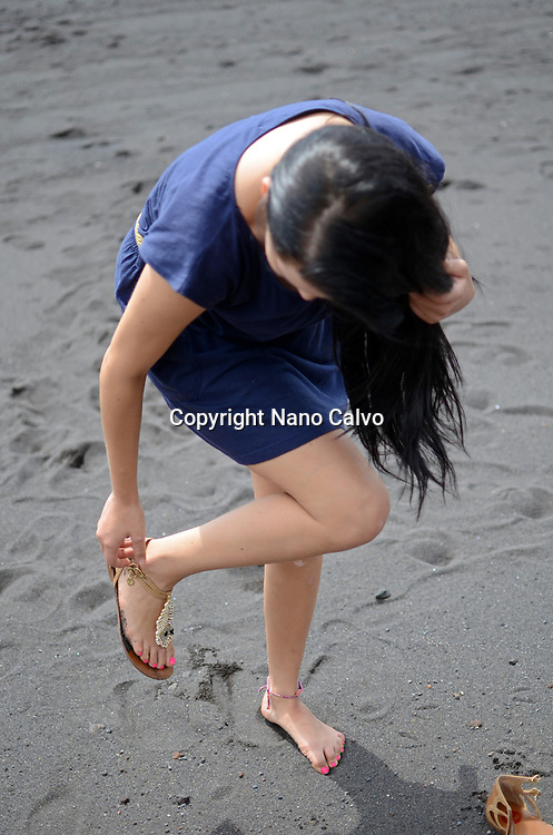 Brunette teenager on the beach, putting her shoes on