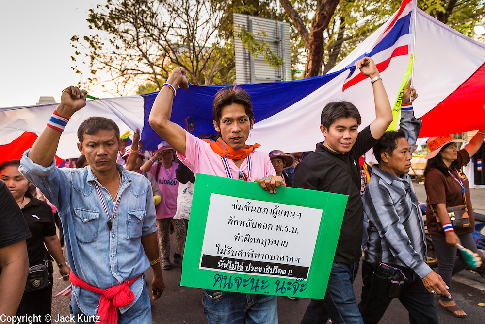 17 JANUARY 2014 - BANGKOK, THAILAND:  Anti-government protestors carry a Thai flag up Rama I Road in Bangkok. Friday was day 5 of the anti-government Shutdown Bangkok protests. The protest, led by the People's Democratic Reform Committee, is calling for the suspension of elections pending political reform in Thailand. There was violence at several sites in Bangkok Friday, including running battles between government opponents and supporters at one site and an IED attack by unknown assailants on anti-government protestors at another site.   PHOTO BY JACK KURTZ