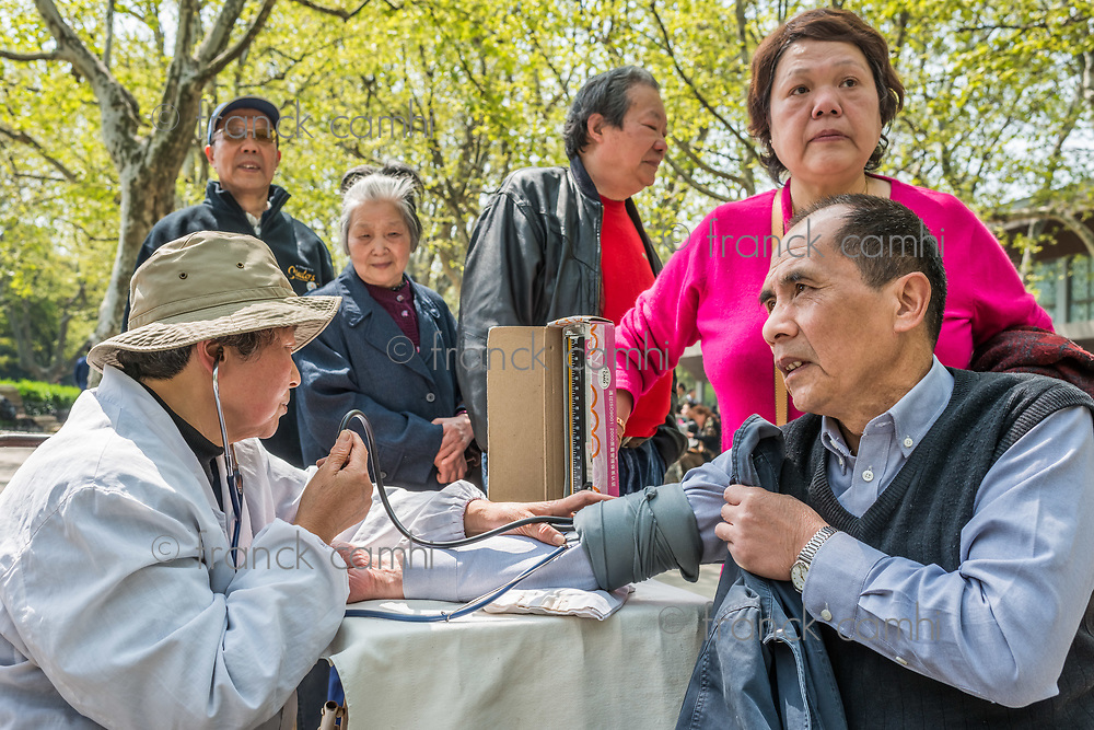 Shanghai, China - April 7, 2013: chinese doctor ausculting people in fuxing park at the city of Shanghai in China on april 7th, 2013