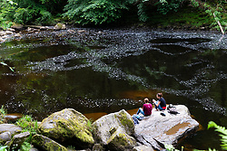Two women sitting on riverbank of River Braan at The Hermitage in Perthshire, Scotland, UK