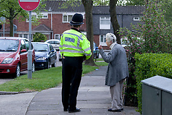 © Licensed to London News Pictures. 11/05/2013. Birmingham, UK. The scene in Cockshut Hill, Yardley, Birmingham, after a man was shot dead outside the Dovecote Public House. Pictured, a Police Officer reassures a concerned resident opposite the place of the shooting. Photo credit : Dave Warren/LNP