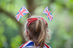 © Licensed to London News Pictures. 11/06/2016. London, UK. A girl wears Union Jack flags in her hair as she waits for the start of Trooping the Colour on Pall Mall. Trooping the Colour, a military parade of the Queen's Household Division, takes place annually and this year marks Her Majesty's  official 90th birthday. Photo credit: Rob Pinney/LNP