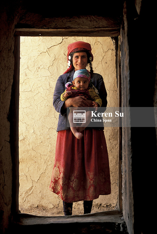 A Tajik woman with her baby by the door of her clay house, Pamir Plateau, Xinjiang Province, Silk Road, China