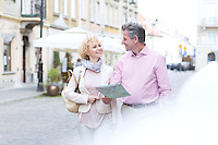 Smiling middle-aged couple with map looking at each other while walking in city