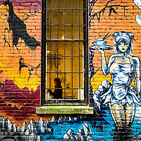 A woman in a window of a brightly painted building