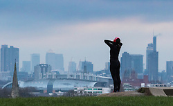 Primrose Hill, London, February 15th 2015. A woman stretches against the backdrop of London's skyline on a chilly early morning on Primrose Hill, overlooking London's skyline.<br /> ///FOR LICENCING CONTACT: paul@pauldaveycreative.co.uk TEL:+44 (0) 7966 016 296 or +44 (0) 20 8969 6875. ©2015 Paul R Davey. All rights reserved.