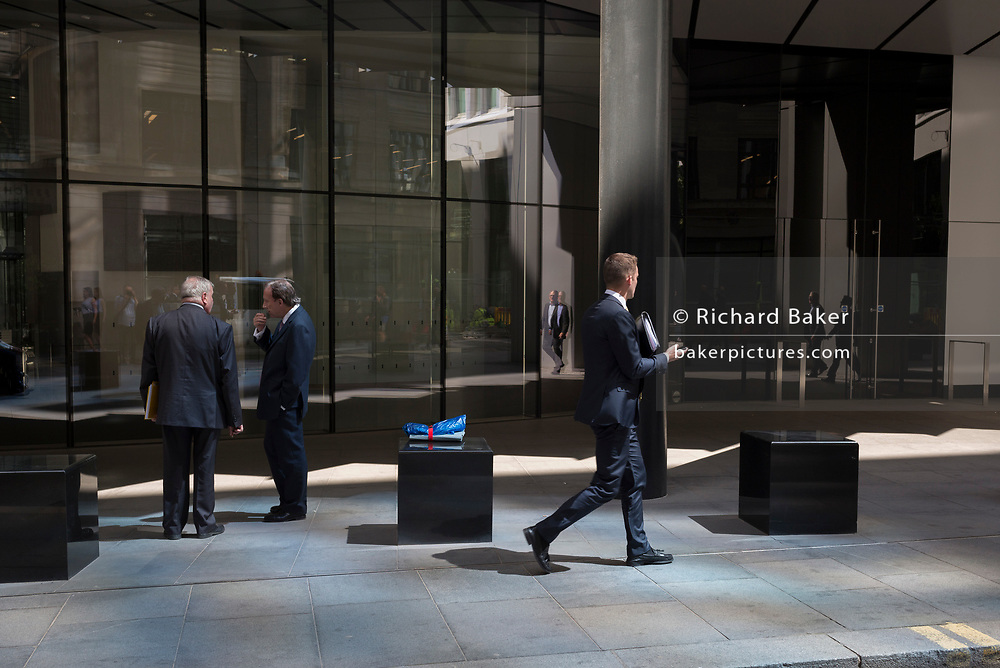 Financial services business people walk through reflected light from a nearby skyscraper in the City of London, the capital's financial district aka the Square Mile, on 17th May 2018, in London, UK.